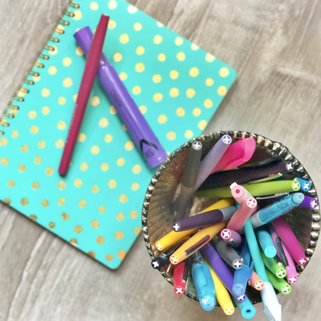 colorful pens and turquoise notebook